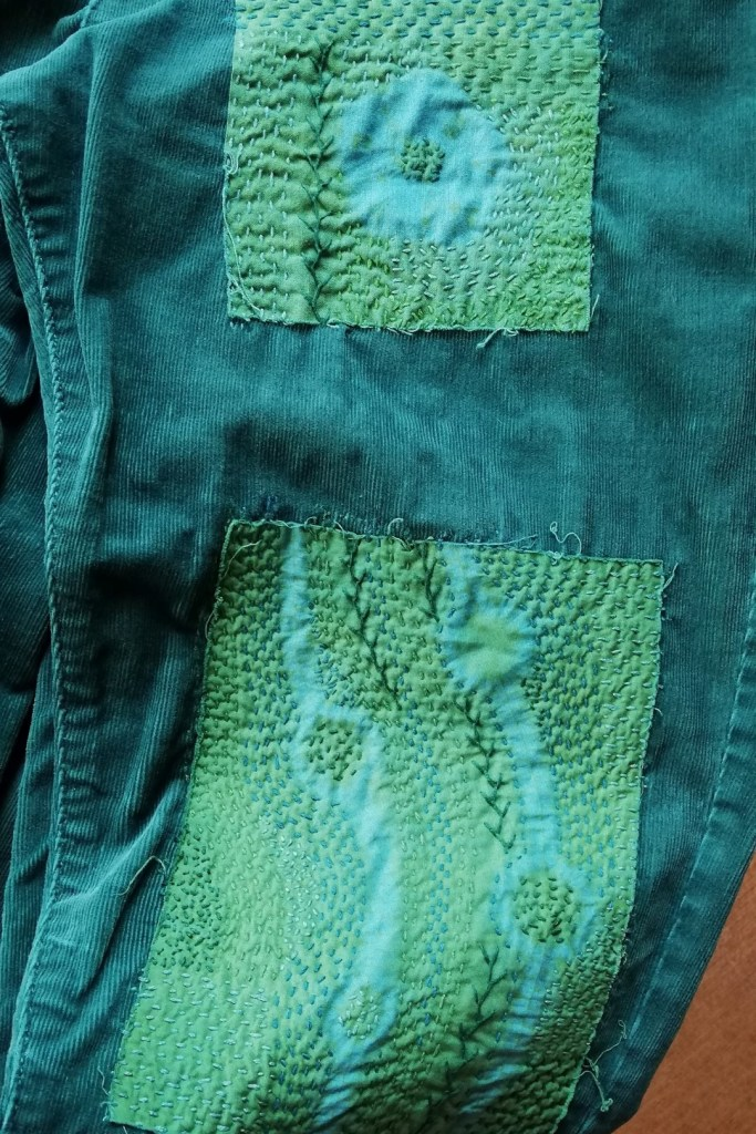 shows dark green jeans with two shibori embroidered patches after overdyeing