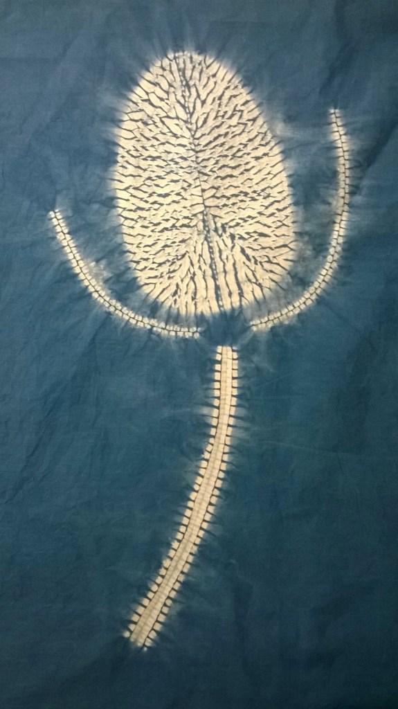 white design on ablue background of a miru shibori teasel