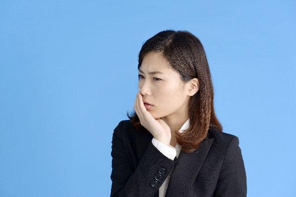 口内炎の痛みで口を押える女性