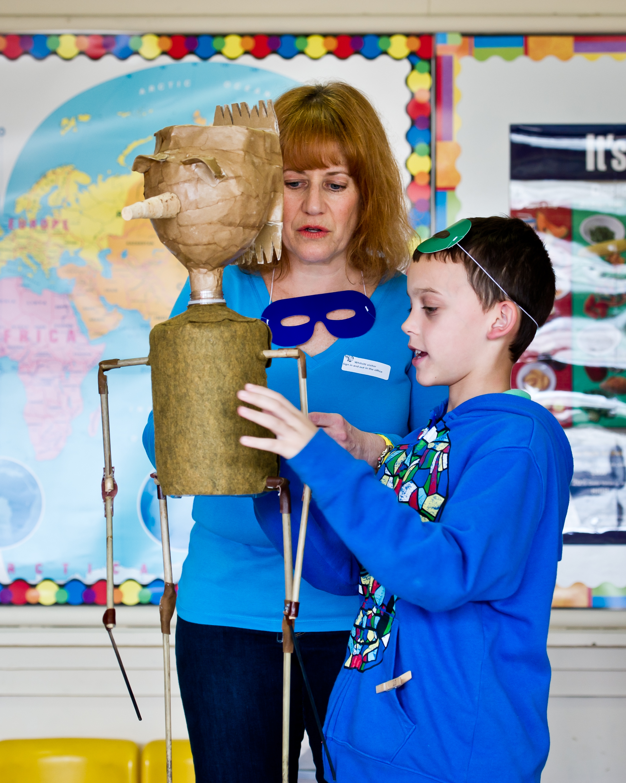 Woman and boy examining puppet