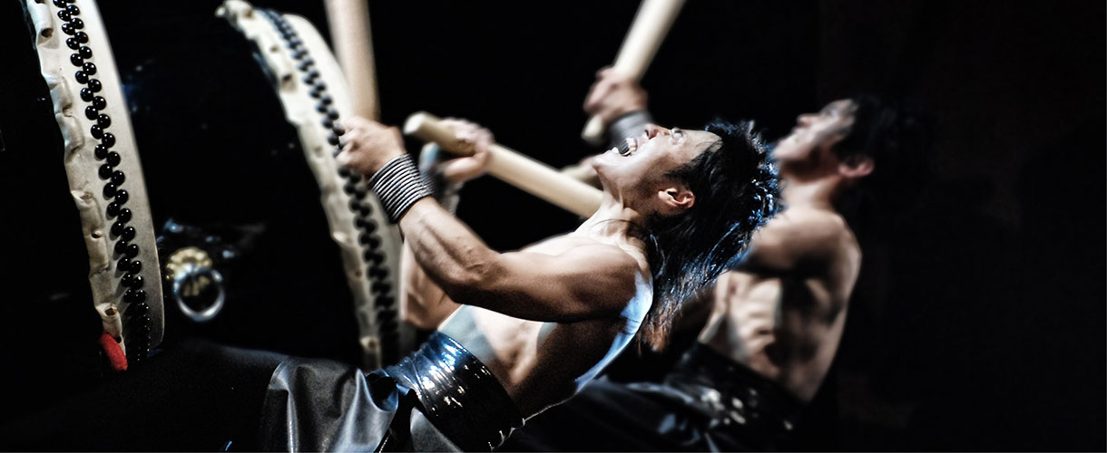 Two Japanese male drummers pound drums