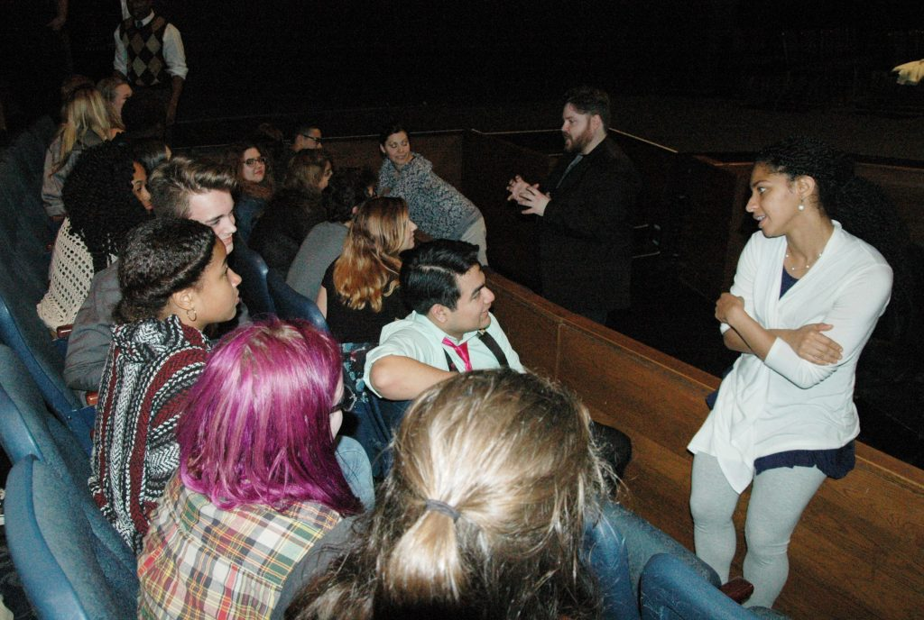 Students in a theater, discussing the show with the performer.