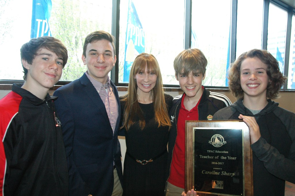 Teacher with students and an award plaque