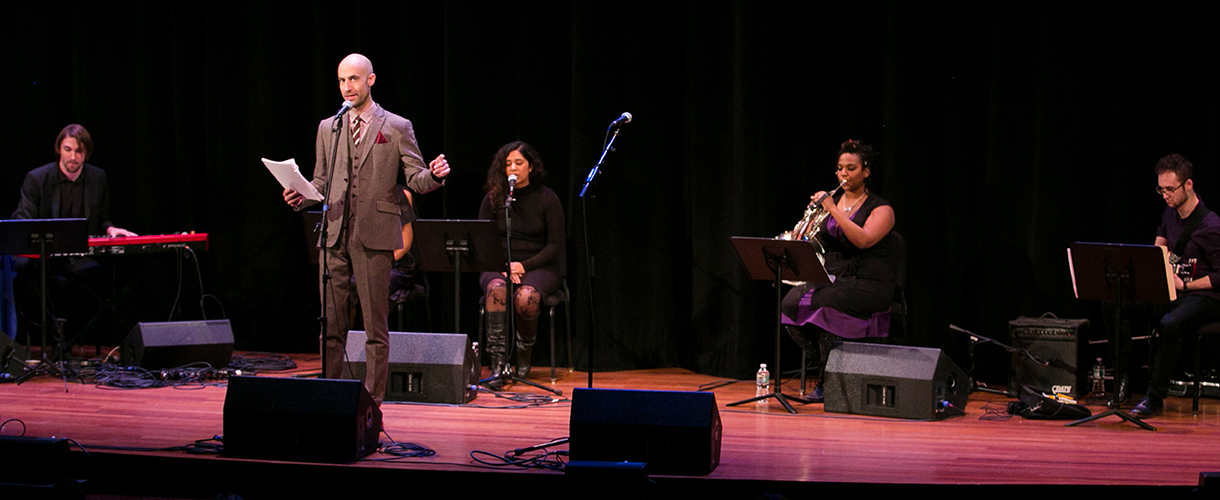 Cecil Baldwin performs on stage at a microphone while musicians perform behind him during Welcome to Night Vale