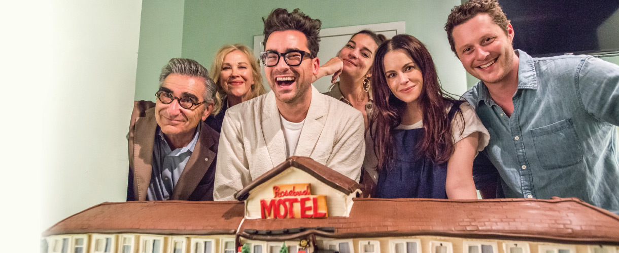 This cast of Schitt's Creek smiling in a group photo.