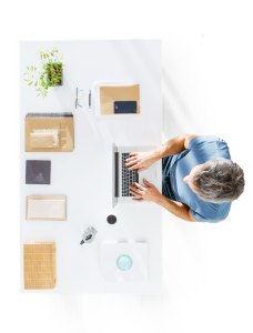 Photo of professional temp worker sitting at his desk working on a laptop