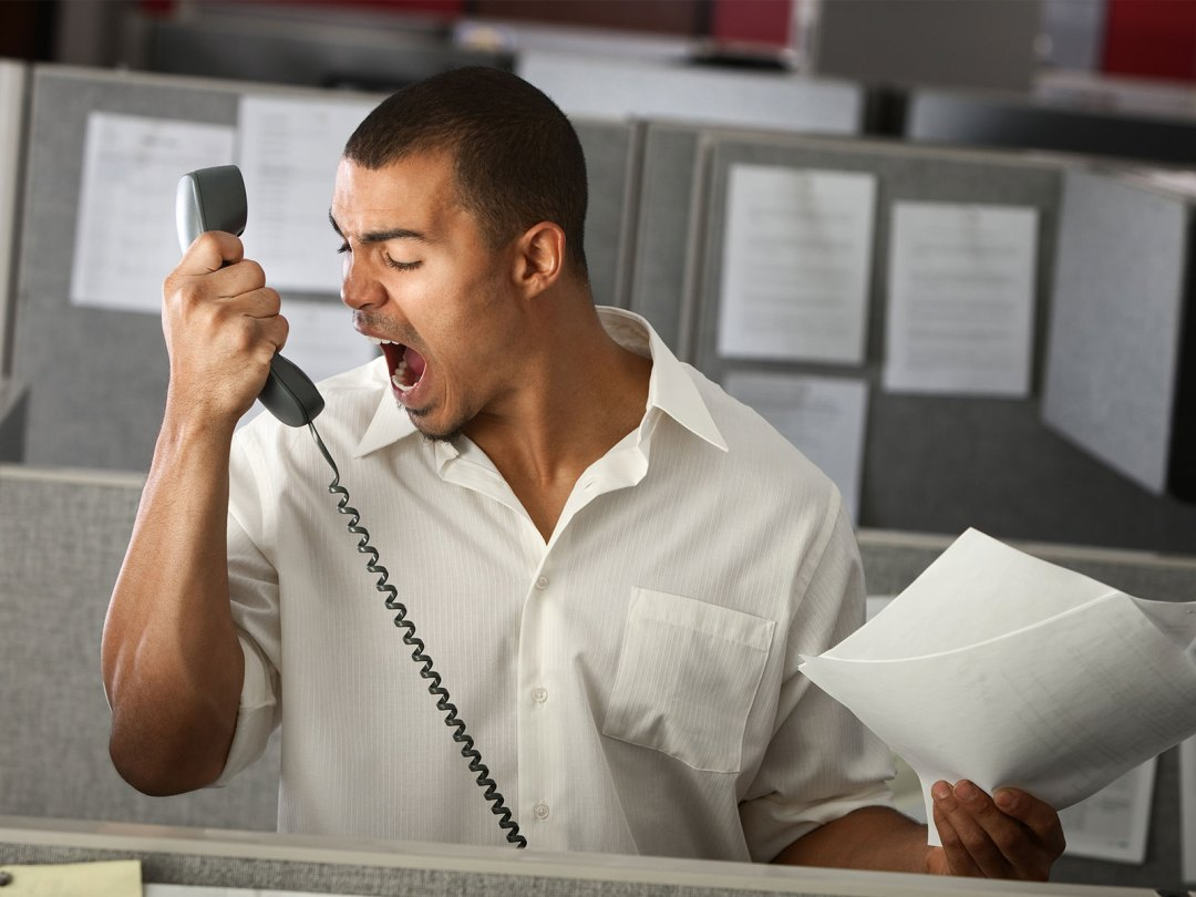 Picture of a male worker screaming at the telephone because his company is understaffed and he is overworked.