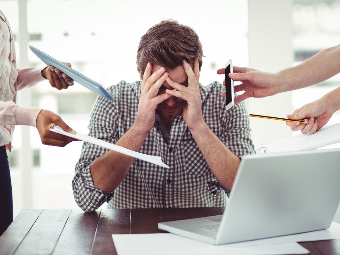 Picture of a male worker feeling overwhelmed at work by contstant demands.