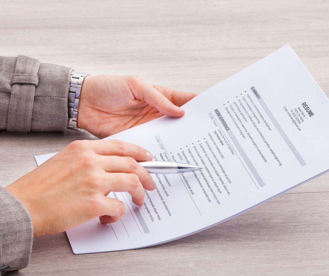 Picture of a person holding a resume.