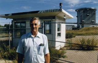 1997, John Armstrong (ret. Warrant Officer, Radar Tech, now deceased), standing before the guardhouse and radar tower atop the hill at the station.