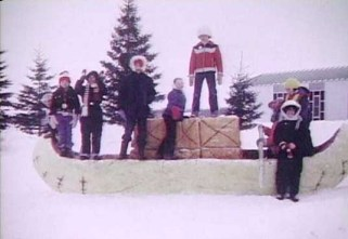 Winter carnival. Proud kids seen here who made snow sculpture for the yearly festival. Chapel in background. CFS Dana, Saskatchewan.