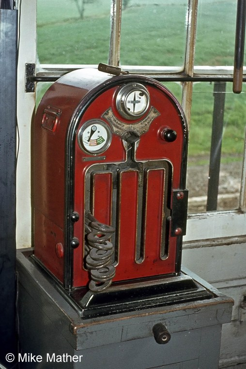 The Tyers Electric Key Token instrument at High Dyke. This instrument allowed a key token to be issued to the driver of a train which was to travel on the single line to Colsterworth as authority to use the single line. There was an identical instrument at Colsterworth signal box, and the two were electrically connected so that only one key token could be removed from the pair of instruments. Once a key token has been withdrawn from either instrument both instruments become locked until the token is replaced in eithe of them. Thus a driver who has been given a token knows that there can be no other train on the section. Photograph by Mike Mather
