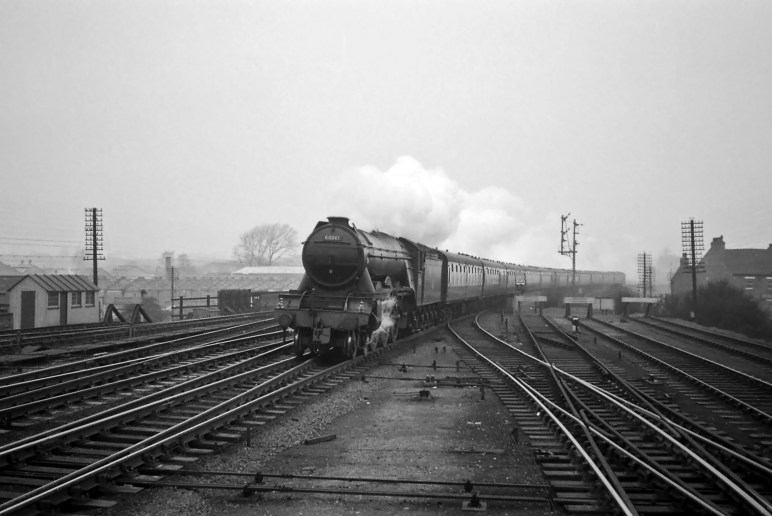 This photograph was taken from the north end of the Up (southbound) platform, opposite Grantham North box (which was just off shot to the left). It's not possible to reach this spot today because the Up platform was cut short in the late 1960s. The first coach of this southbound train on the Up Main line, hauled by No.60061 Pretty Polly, is passing over the connection to the Up Bay platform. The Nottingham lines are converging into the Main lines from the left. We can see that the train is not stopping at the station because both the Grantham North box Up Main home signal and, beneath it, the Grantham Yard box Up Main distant signal are showing 'clear'. To the right of the Main Line signals is the signal for the Up Bay platform. It's worth pointing out here the two lines of telegraph poles, one on each side of the railway, which used to be so much part of the everyday railway scene. These pole routes carried the block telegraph, the 'speaking' (single needle) telegraph, telephone and other circuits on which the railway depended for the communication vital to effective operation. It was the responsibility of the Signal and Telegraph (S&T) Engineers and Technicians to maintain this widespread network and also to keep the signals maintained and in working order. It was a job that often involved working at height exposed to the worst of the weather. Photograph by Noel Ingram, used with permission from Steam World.