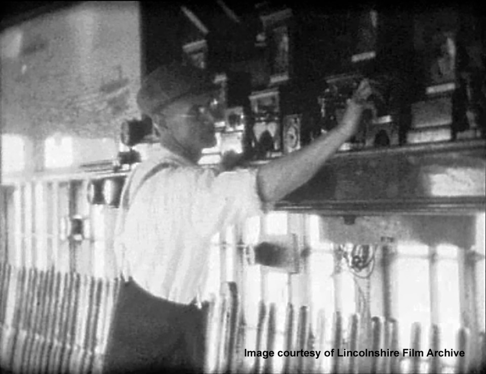 The signalman is communicating with one of the neighbouring boxes by special code using electric bells. From a film shot by Walter Lee. © Lincolnshire Film Archive