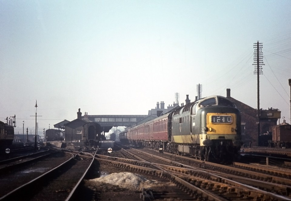 This is the approach to the station from the south in the early 1960s. It was taken from between the Main lines, on the right, and the Down Slow line on the left. Beyond the Down Slow line is Carriage Siding No.1. The roof of Grantham Yard box can be glimpsed above the front of the first coach of the approaching train. All the connections with the line which crosses diagonally from the bottom right corner to the Western platform on the left were under the control of Grantham Yard box. The disc signals facing the camera control shunting movements towards the station platforms. On the right the lofty pole route carries telegraph and telephone communication along the eastern side of the railway. Photograph by Noel Ingram, used with permission from Steam World.