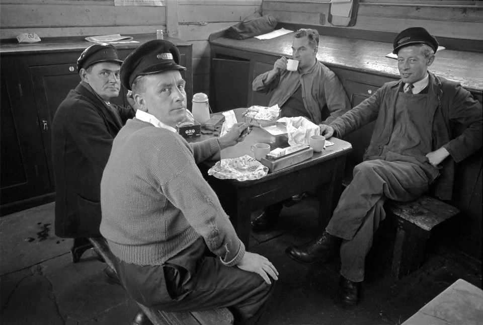 Taking a break in the Passenger Shunters' cabin at the south end of the 'down' platform on 15th August 1963. On the table, among the lunch boxes and tea cans, are a cribbage board and a set of dominoes. Left to right: Driver Albert Bottomley, Passenger Shunter Gilbert Needham, Driver Ted Matsell and Passenger Shunter Dennis (Dick) Knight. Passenger Shunters assisted with locomotive changes and arranged the coaches in the carriage sidings at the south end of the station into train formations. Photograph by Cedric A. Clayson, © John Clayson