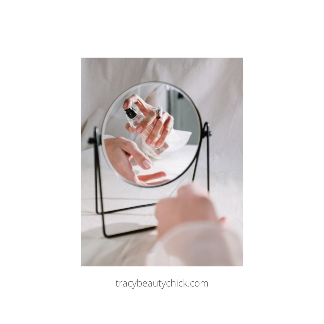 Photo of ladies wrist in a mirror spraying fragrance on the wrist.