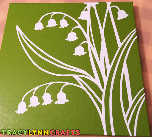 Vinyl stencil is removed showing the high contrast of the lily of the valley design on the darker green canvas panel