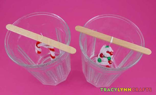 Suspend the ornaments in the glass containers so that they are not touching the sides of bottom