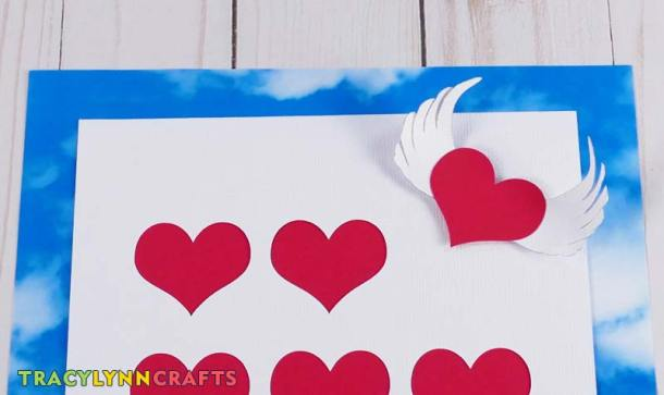 Attach the silver-tipped soaring wings to the shadow box heart art project