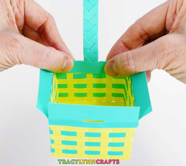 Insert one end of the handle into the slit and glue the flap to the inside of the basket
