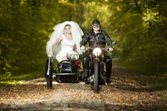 Bride And Groom Driving To Their Wedding In A Motorcycle