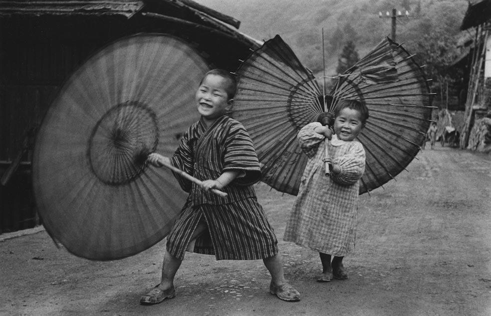 """""""Bambini che fanno roteare gli ombrelli"""", 1937 circa, dalla serie """"Bambini (Kodomotachi)"""" Ogōchimura 535 x 748 mm. (Ken Domon Museum of Photography)"""