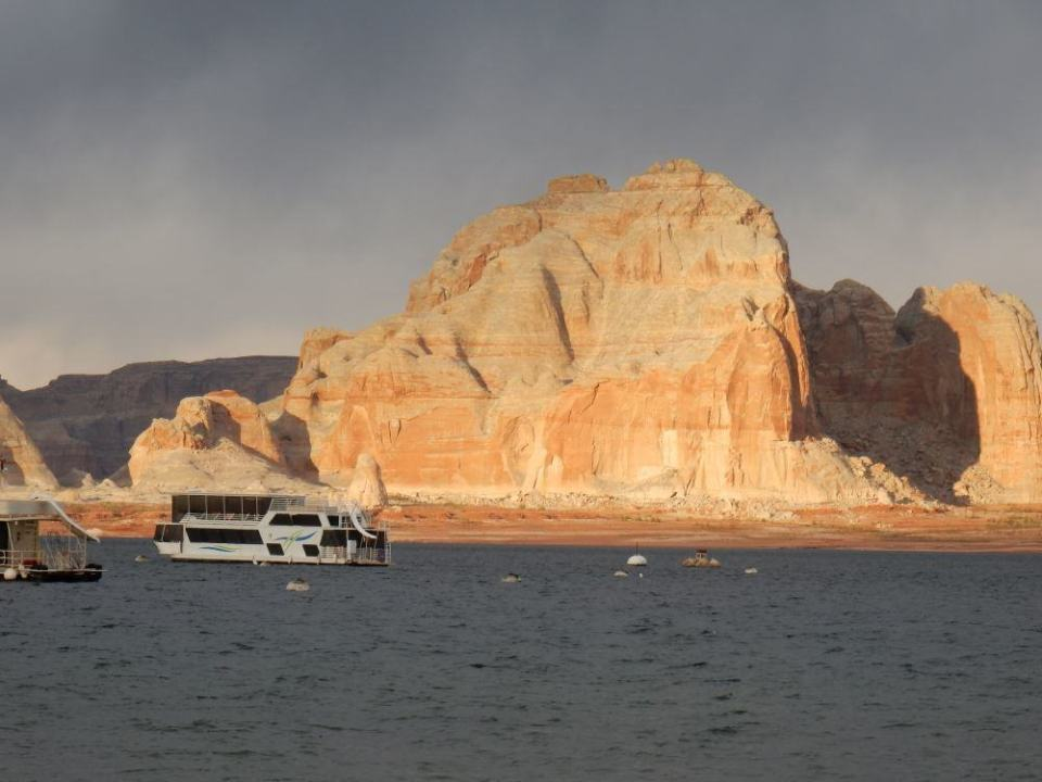 Sunset lights up the rocks on lake Powell. Lots of boats sit in the bay.