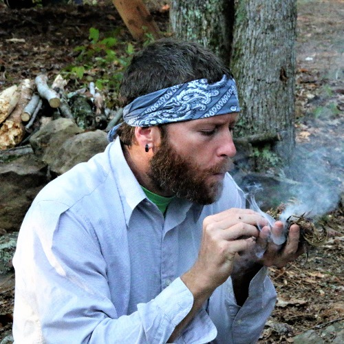 student at survival school blowing ember into a fire during survival training