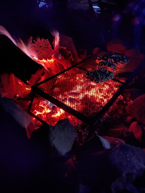 food cooking on a camp fire