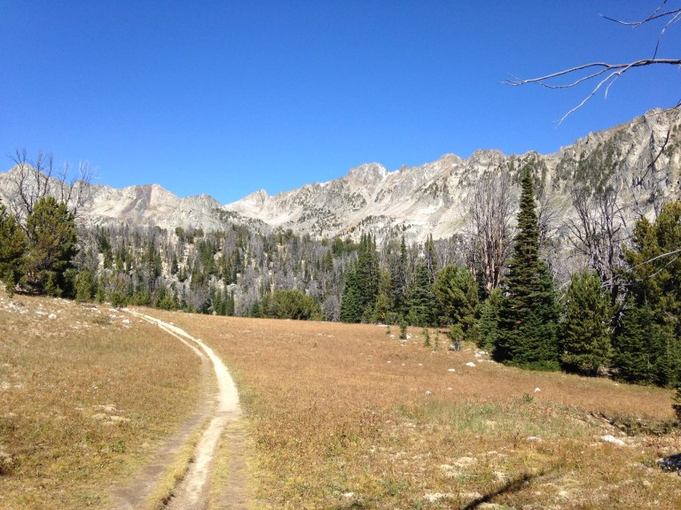 The trail winding through a basin with spectacular surrounding mountains