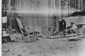 A man leaning back in a chair smoking a pipe with four other men sitting around a campsite.