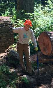 A smiling woman standing between the cut ends of a log with her foot on a partially buried boulder in front of her.