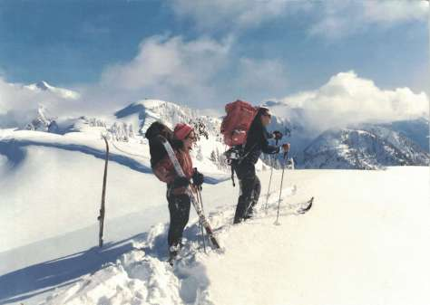 A man on skis and a woman who has taken off her skis stand in deep snow on a ridgeline and look out at a view of snowy mountains.
