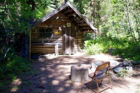 A small log cabin in a clearing with a rusted folding chair facing it.