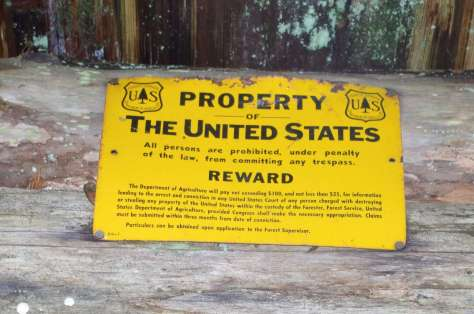 """A large rusting yellow metal US Forest Service sign nailed to logs, stating """"Property of the United States. All persons are prohibited, under penalty of the law, from committing any trespass."""""""