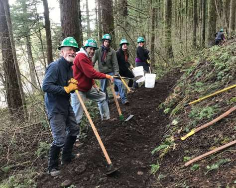 Five people in green hard hats stand downhill of a trail with their trail tools in front of them on the trail tread.