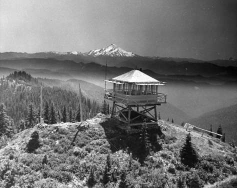 A cabin on stilts in the foreground with a snowy peak in the background.