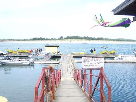 A ramp leading down to a dock where around a dozen small boats with outboard engines are moored.
