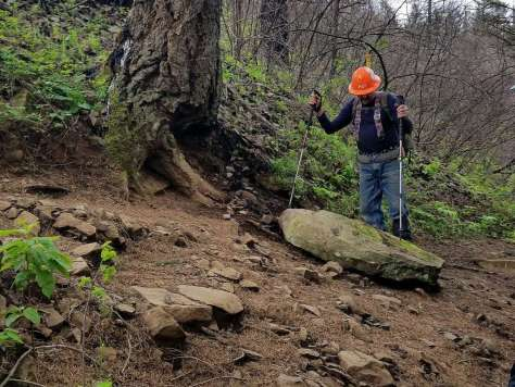 A trail worker in a hard hat stands looking down at a large rock.