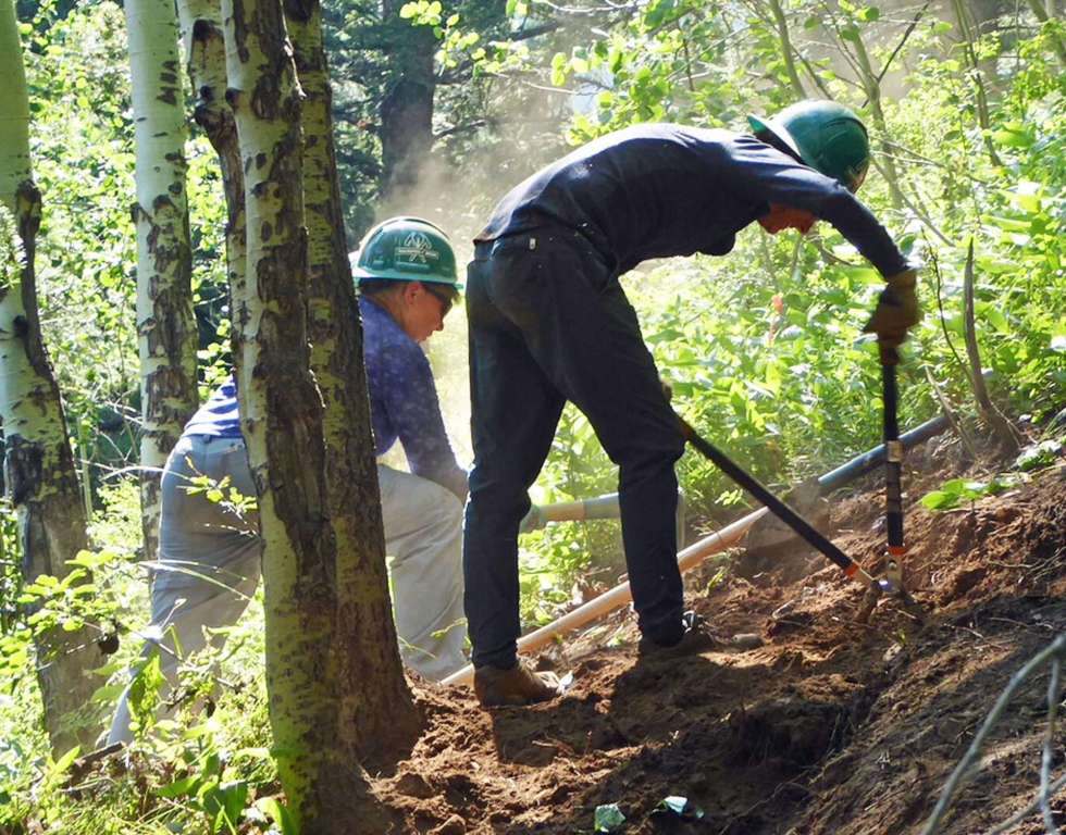 Two workers in hardhats apply tools to a trail on steep terrain.