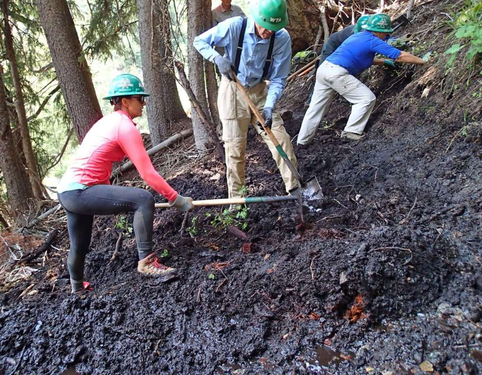A man and a woman dig into mucky soil on a hillside.