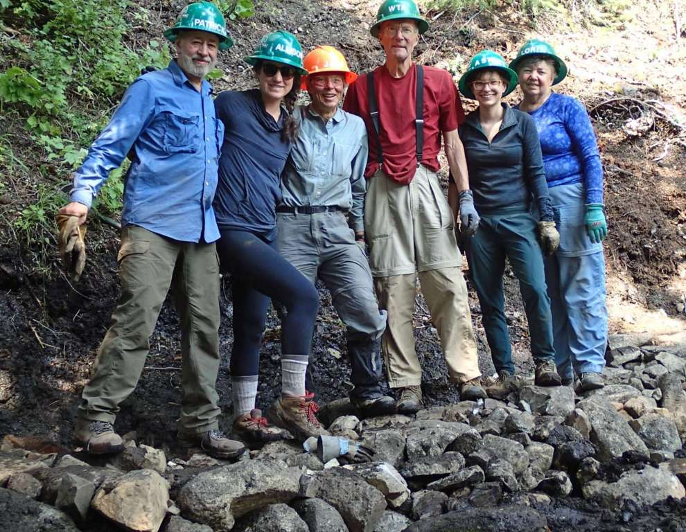 Six men and women standing on a level trail of rocks.