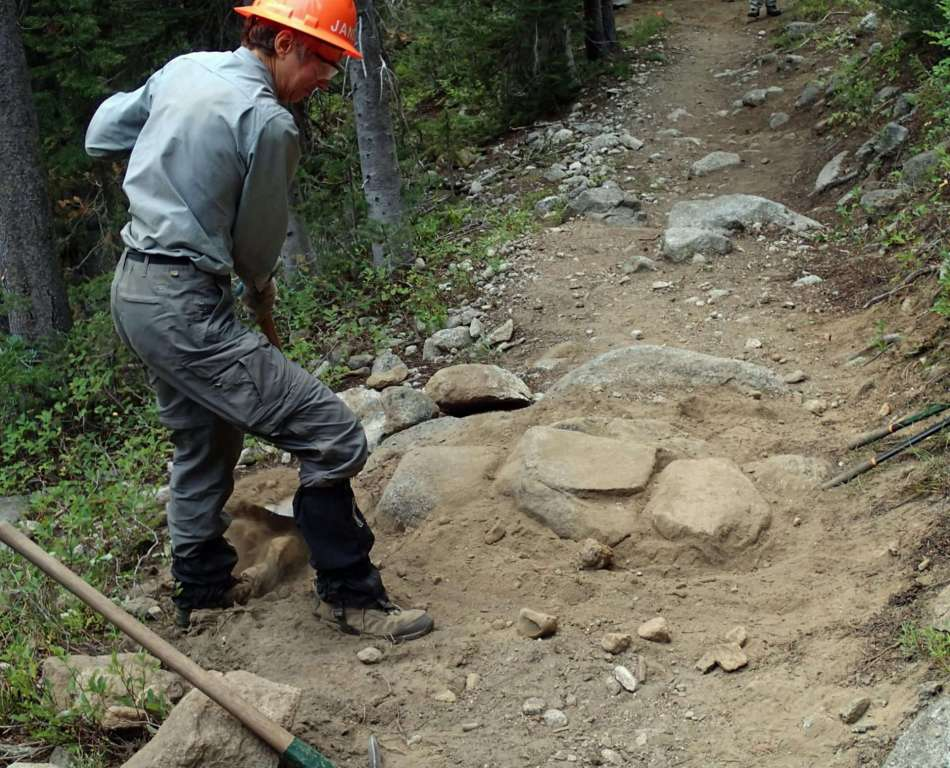 A hard-hatted man standing above several boulders and a small trench crossing a trail