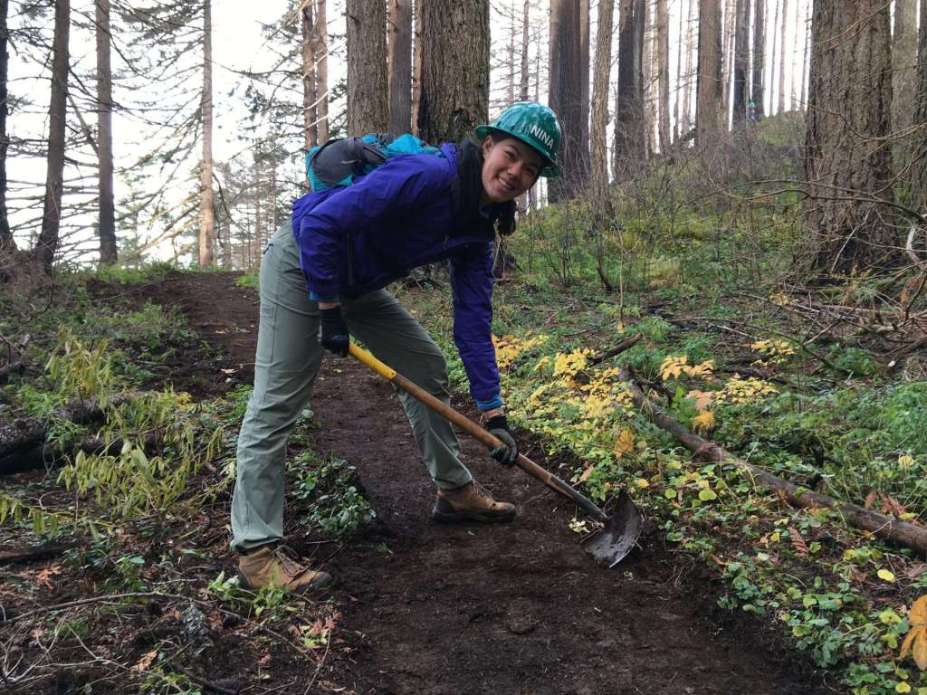 A woman in a hard hat leans over a trail in a wooded area while pulling the blade of a long-handled tool across the tread.