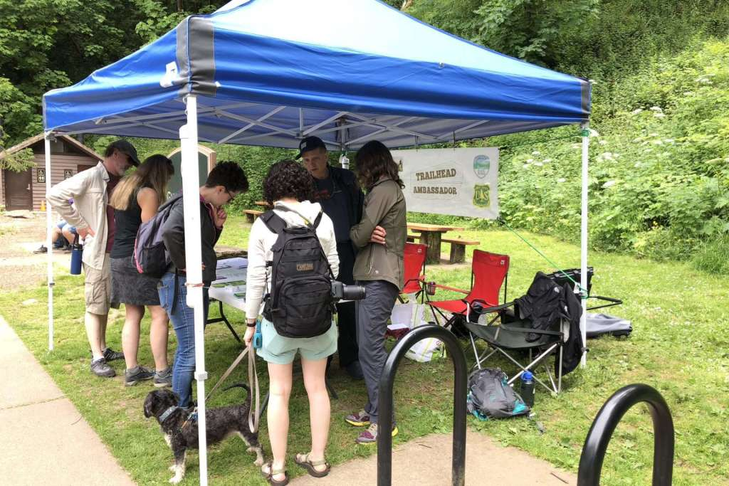 """A group of adults stand around a table under a tent with a """"Trailhead Ambassador"""" banner in front of a green forest."""