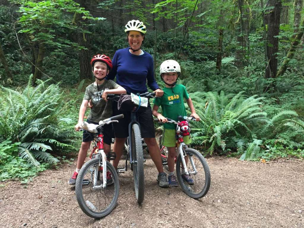 A woman flanked by a boy on either side, all smiling as they sit astride bicycles against a green backdrop of sword ferns and trees.