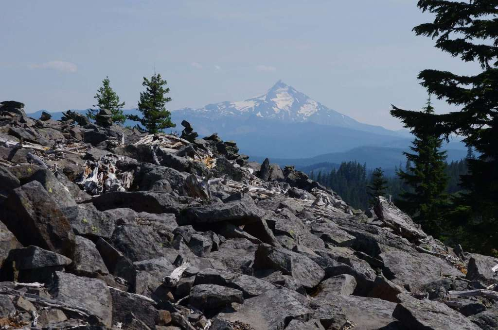 A hillside of jumbled rock with a snowy volcanic peak in the distance.