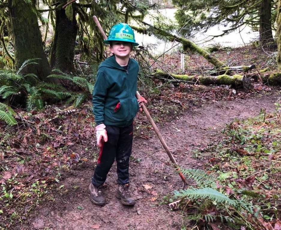 A young boy wearing a hardhat holds a rake on a trail.
