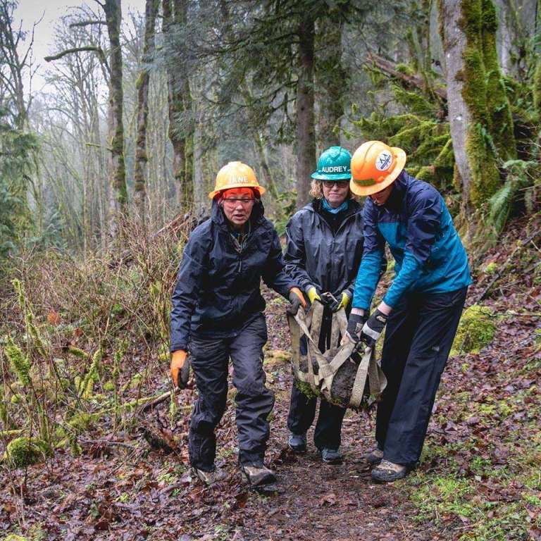 Three women in hardhats carry a log along a trail.